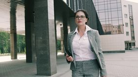 Young business woman walking to the office building stock footage