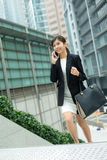 Young business woman walking up the step and chat on mobile phone royalty free stock photography