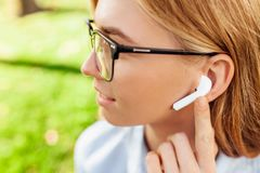 Young girl in glasses listening to music through wireless headphones outdoors royalty free stock photo