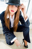 Young business woman wearing man's suit, hat and high heels in office. Pretty business woman looking bossy wearing man's suit, stylish hat and high heels in Royalty Free Stock Image