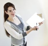Smiling Young Business Woman shows White Clipboard. A smiling pretty  young businesswoman holding a blank clipboard Stock Image