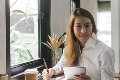 Young business woman in white dress sitting at table in cafe and writing in notebook. Asian woman using tablet. Stock Photography