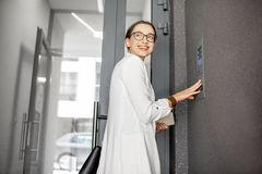 Woman entering code on the building entrance royalty free stock photography
