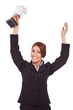 Young business woman winning a trophy. Portrait of an excited young business woman winning a trophy against white background Royalty Free Stock Images