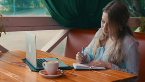 Young business woman work in cafe using laptop writing in notebook. 4K stock footage