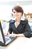Young business woman work on laptop. In interiors Royalty Free Stock Photo