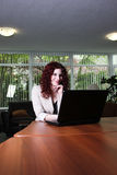 Young business woman at work with laptop computer. Attractive woman at the office working on a laptop computer Royalty Free Stock Photo