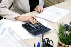 Young business woman working hard over the Desk in the study, economist accountant financial reporting, verifies accuracy of docum Stock Photography