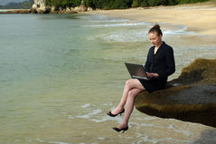 A young business woman working on her laptop at the beach Royalty Free Stock Photography