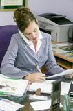 Young business woman working in her office. A young woman in a business suit busy working in her office whilst talking on the telephone Royalty Free Stock Photo