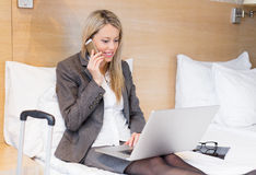 Young business woman working with laptop computer in hotel room Stock Photos