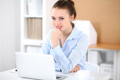 Young business woman working on laptop in office. Successful business concept. Young business woman working on laptop in office. Successful business concept Stock Image
