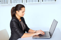 Young business woman working on a laptop. Portrait of beautiful young brunette business woman working on a laptop in office Royalty Free Stock Photo