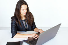 Young business woman working on laptop. Portrait of beautiful young smiling brunette business woman working on a laptop in office Stock Photo