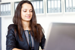 Young business woman working on laptop. Portrait of beautiful young smiling brunette business woman working on a laptop in office Royalty Free Stock Image