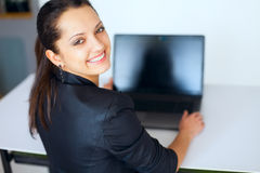 Young business woman working on a laptop. Portrait of beautiful young smiling brunette business woman working on a laptop in office,looking back Royalty Free Stock Photography