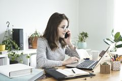 Young business woman working on laptop and talking mobile phone in office. royalty free stock photography