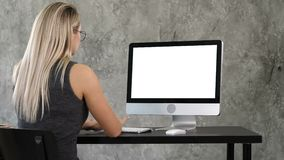 Young business woman working in office interior on pc on desk, typing, looking at screen. White Display.