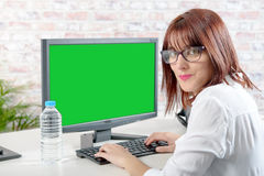 Young business woman working at pc with green screen. Pretty young business woman working at pc with green screen Stock Photos