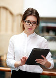Young business woman working at tablet standing indoor Royalty Free Stock Photo