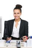 Young business woman writes into a file. Young, beautiful business woman sits at the desk in the office and writes into a file Stock Image