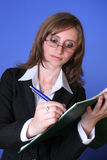 Young business woman writing. Image of a young business woman writing in a file , with a concentrated expression on her face,suggesting work and responsability Royalty Free Stock Photography