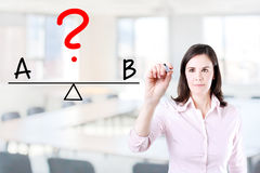 Young business woman writing A and B compare on balance bar. Office background. Young business woman writing A and B compare on balance bar. Office background stock photography