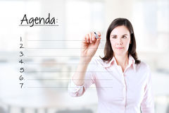 Young business woman writing blank agenda list. Royalty Free Stock Photos