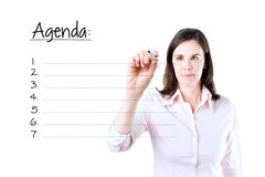 Young business woman writing blank agenda list. Stock Photo
