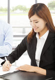 Young business woman writing document with colleague Stock Photography