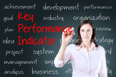 Young business woman writing key performance indicator (kpi) concept. Blue background. Royalty Free Stock Image