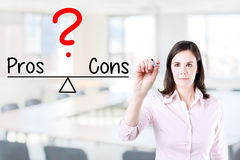 Young business woman writing pros and cons compare on balance bar. Office background. Royalty Free Stock Photo