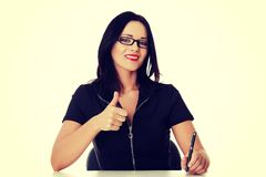 Young business woman writing and showing ok. Stock Photos