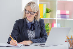 Young business woman writing to do list while sitting at her desk Stock Image