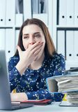 Young business woman yawning at a modern office desk in front of laptop, covering her mouth. Overworked woman. stock photo