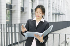 Young business women with binder. Young chinese secretary or businesswoman in suit with notebook Stock Photography
