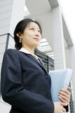 Young business women with binder. Young chinese secretary or businesswoman in suit with notebook Royalty Free Stock Images