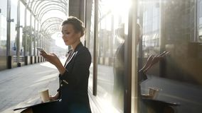 Business women on street. Young business women in black jacket siting and talking on phone, smile and relax in sun light, middle shot
