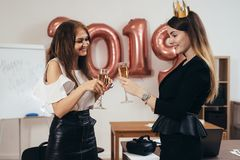 Young business women celebrating Christmas, New Year in office royalty free stock photography