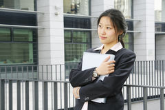 Young business women with file. Young chinese secretary or businesswoman in suit with notebook Stock Images