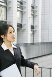 Young business women with file. Young chinese secretary or businesswoman in suit with notebook Royalty Free Stock Photos