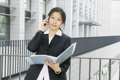 Young business women with file. Young chinese secretary or businesswoman in suit with notebook and mobile phone Stock Photo