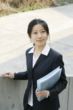 Young business women with file. Young chinese secretary or businesswoman in suit with notebook Royalty Free Stock Images
