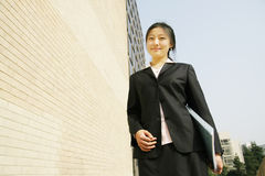 Young business women with file. Young chinese secretary or businesswoman in suit with notebook Stock Photos