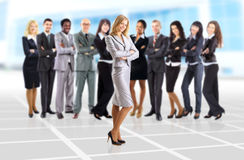 Business woman and her team  over office background. Young business women and her team  over office background Royalty Free Stock Images