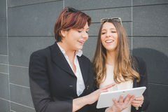 Young business women looking at digital tablet pc in the city Royalty Free Stock Photo