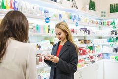 Young business woman in perfumery shop choose cosmetics with consultant. Young business women in perfumery shop choose cosmetics with consultant Stock Photos