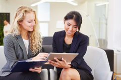 Young business women planning in teamwork. Young business women planning meeting in teamwork with tablet Royalty Free Stock Photos