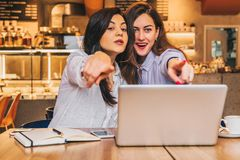 Young business women are sitting in a cafe. Girls with joyful surprise point fingers at what they see outside the window. Two young business women are sitting in Royalty Free Stock Photography
