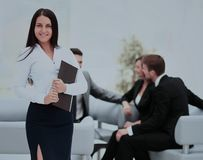 Successful business man standing with his staff in background at Stock Photography